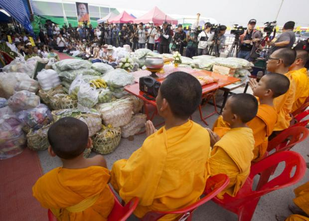 A merit-making rite takes place at Klong Luang market as monks and novices from Wat Phra Dhammakaya leave the temple grounds to collect alms. Some of the devotees brought large amounts of dried food, fruit and vegetables from the market to the temple after monks complained about food shortages.(Photo by Apichit Jinakul)