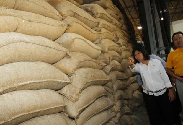 Mrs Duangporn inspects pledged rice being stored at a warehouse in Nakhon Pathom province. State-held rice stocks have recently fallen to 5.04 million tonnes. TAWATCHAI KEMGUMNERD