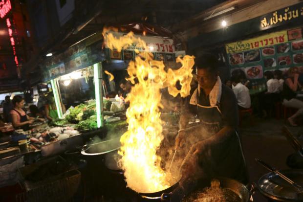 Vendors prepare food at food stalls at Chinatown's Yaowarat Road. (Photo by Patipat Janthong)