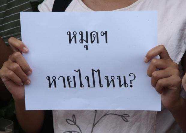 An activist holds a piece of paper which reads: 'Where has the plaque gone?'Thiti Wannamontha