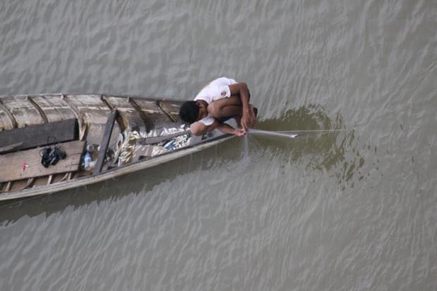 A fisherman lays down his net in Tonle Sekong River, a tributary of the Mekong River, in Cambodia. The river is the site of several new dams, helping power Cambodia's emerging economy.