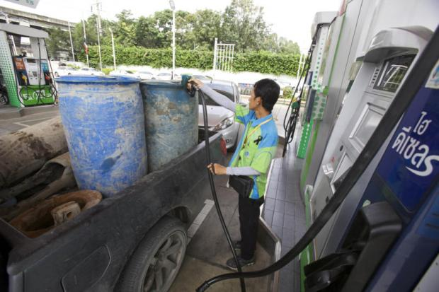 A man refills a pickup truck at a petrol station in Bangkok. Removal of fossil fuel subsidies can bring economic, social and environmental benefits in the long run.APICHIT JINAKUL