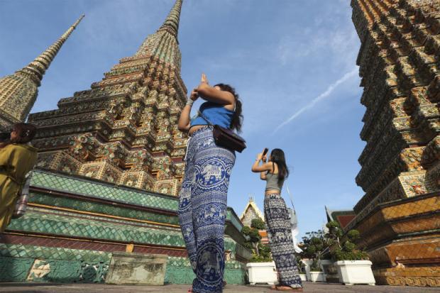 Tourists take photos at Wat Pho, the Temple of the Reclining Buddha. PATIPAT JANTHONG