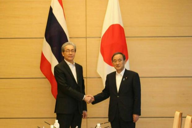 Deputy Prime Minister Somkid Jatusripitak (left) shakes hands with Japan's Yoshihide Suga, chief cabinet secretary. The pact with Japan is seen as vital to bringing in Japanese investment to Thailand.