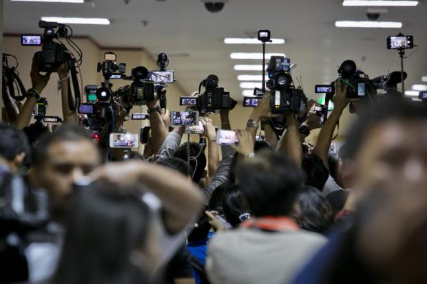 The media crowd the Royal Thai Police headquarters as police question suspects in the murder of a karaoke bar worker.Krit Promsaka na Sakolnakorn