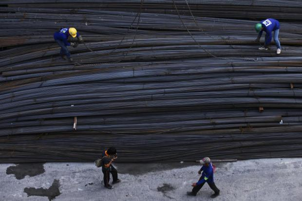 Workers arrange steel rods at a construction site in Bangkok. The Revenue Department aims to make local steelmakers pay their taxes in full.PATIPAT JANTHONG