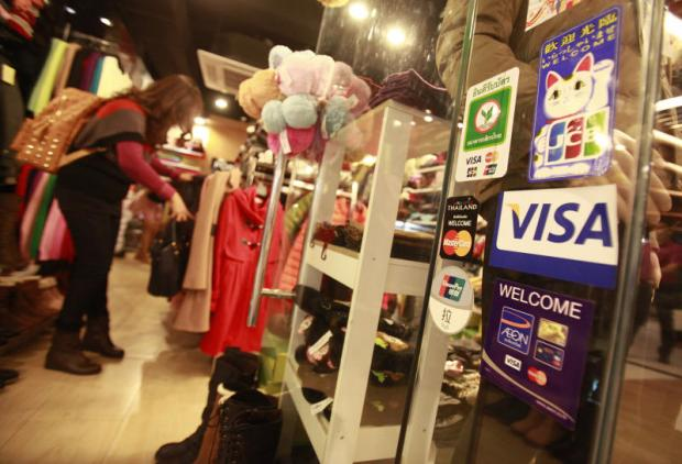 Stickers showing a variety of credit cards accepted are displayed on the door of a shop in Bangkok.THANARAK KHUNTON