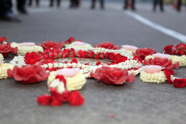 Flowers and garlands placed by activists last year adorn the memorial plaque at the Royal Plaza in commemoration of the 1932 revolution by Khana Ratsadon.Apichart Jinakul