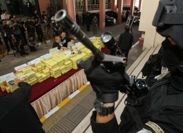 Officials arrange packages of illicit drugs seized in nine cases for a news conference as heavily armed officers stand guard at the Narcotics Suppression Bureau on Vibhavadi Rangsit Road yesterday. More than 5.7 million methamphetamine pills, 40kg of crystal meth and 20kg of heroin were part of the drug haul worth 1.3 billion baht in total.(Photo by Apichit Jinakul)