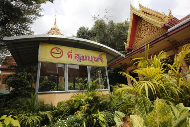 A sign is put up at the entrance to Wat Samian Naree in Bangkok to designate a space for smokers as the latest amendment to the tobacco control law goes into effect. (Photo by Wichan Charoenkiatpakul)