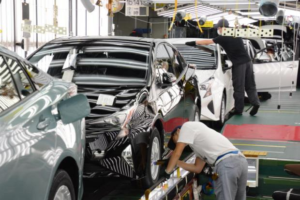 Workers run the assembly line at a Toyota Prius plant in Aichi, Japan. The carmaker plans a huge investment to make hybrid electric vehicles in Thailand.
