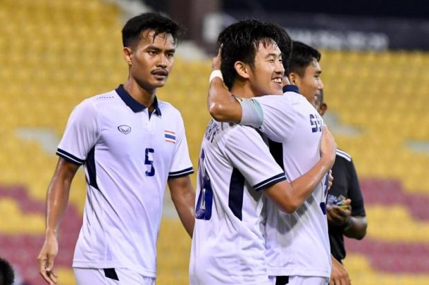 Thailand's Worachit Kanitsribumpen, centre, is congratulated by teammate after scoring the winner against Timor Leste.