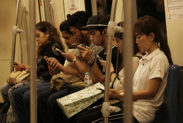 Commuters check mobile devices on an underground train. APICHIT JINAKUL