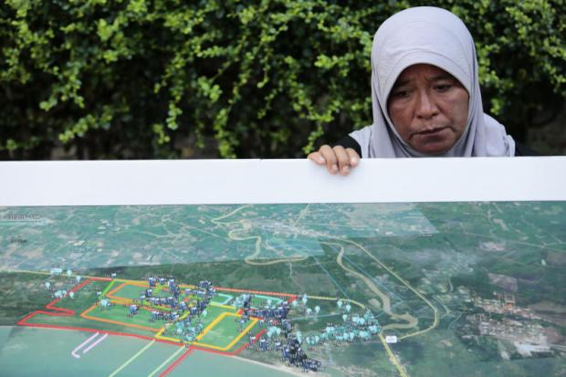 A woman yesterday holds a poster during a protest against the construction of a coal-fired power plant in Thepa district of Songkhla. Patipat Janthong