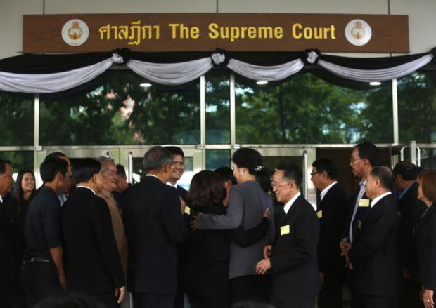 Ousted prime minister Yingluck Shinawatra, centre, appears at the Supreme Court in July for a witness hearing session in the malfeasance case in which she is alleged to have failed to prevent damage and irregularities in the rice-pledging scheme. PATTARAPONG CHATPATTARASILL