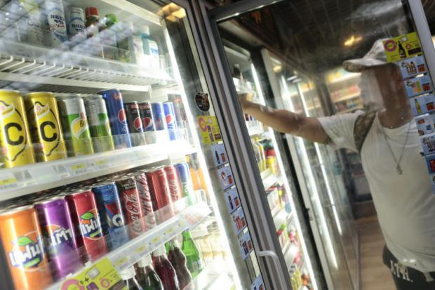 A customer chooses a drink at a convenience store. The excise tax on sugary drinks will take effect gradually.