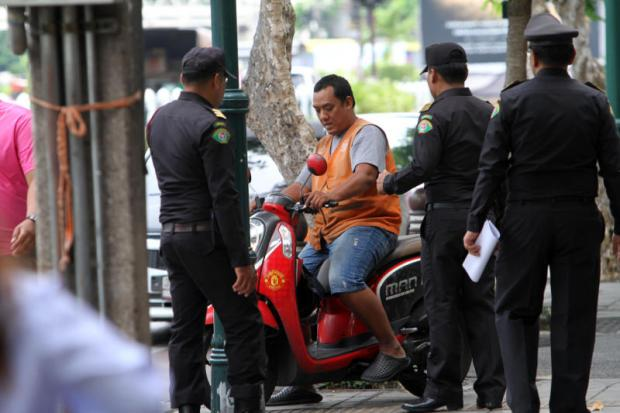 Bangkok municipal officers warn a motorcyclist not to misuse public space by riding along a pedestrian footpath in front of Soi Intarapitak 1 in Thon Buri district.(Photo by Apichart Jinakul)