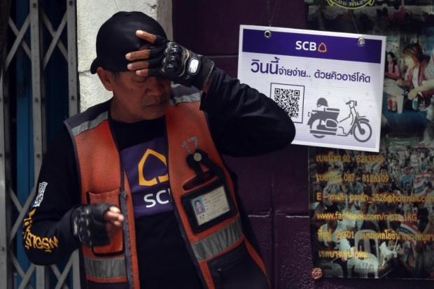 A motorcycle taxi driver stands in front of the board advertising SCB's QR code payment service which is available for payment to motorcycle taxis in Phahon Yothin area.WEERAWONG WONGPREEDEE.