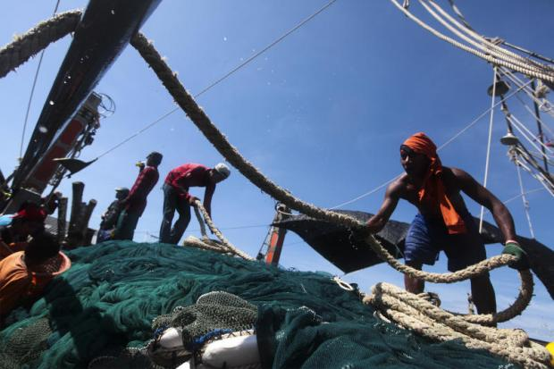 Migrant labourers work on a fishing boat docked at a pier in Phangnga province in southern Thailand. Photo: Patipat JanthongP