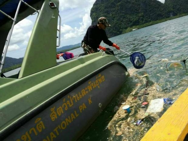 A worker scoops up rubbish from the sea off the coast of Phangnga. photo by the Department of National Park, Wildlife and Plant Conservation