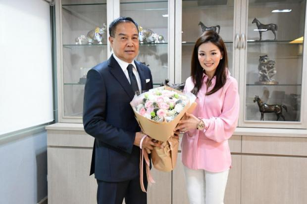 Thai football chief Somyot Poompunmuang gives Watanya Wongopasi a bouquet of flowers yesterday.