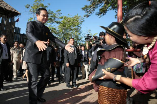 Prime Minister Prayut Chan-o-cha walks toward a boy dressed in traditional costume during his visit to Phra Nakhon Si Ayutthaya historical park in Ayutthaya before chairing the mobile cabinet meeting at Rajabhat University Tuesday. (Photo by Chanat Katanyu)