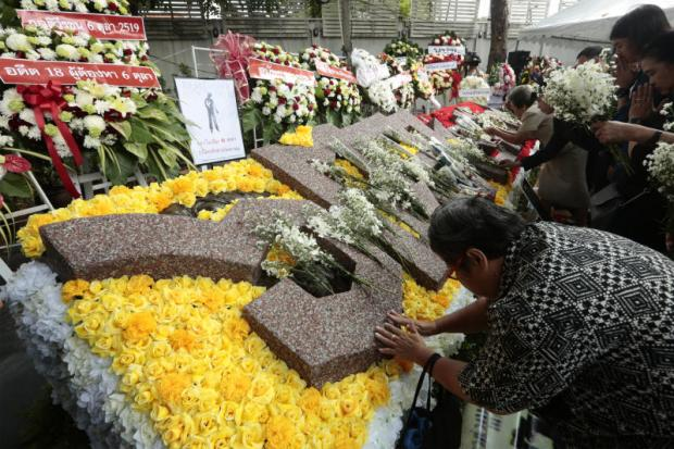 Relatives lay flowers and wreaths at the Oct 6 memorial ground inside Thammasat University's Tha Prachan campus yesterday. Former student activists and academics set up an online archive about the Oct 6, 1976 massacre to raise awareness.(Photo by Patipat Janthong)