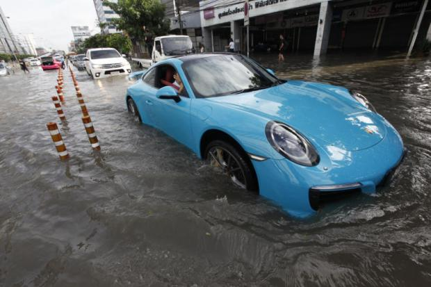 DAMP COURSE: Vehicles crawl along flooded Ratchadaphisek Road on Saturday.