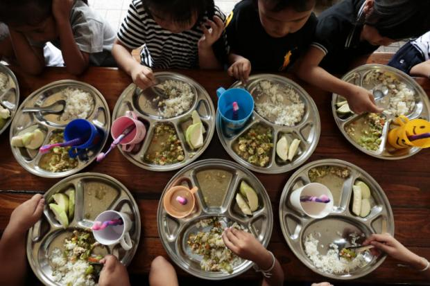 Less privileged children in Klong Toey eat lunch made largely from nearly-expired ingredients donated by a supermarket operator as part of an initiative to cut food wastage.Patipat Janthong