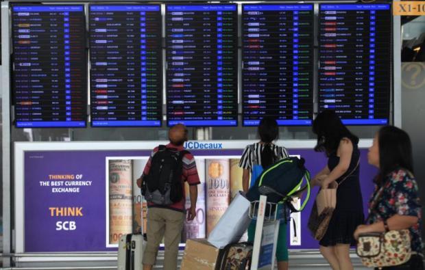 Passengers check the flight information board at Suvarnabhumi airport.SOMCHAI POOMLARD