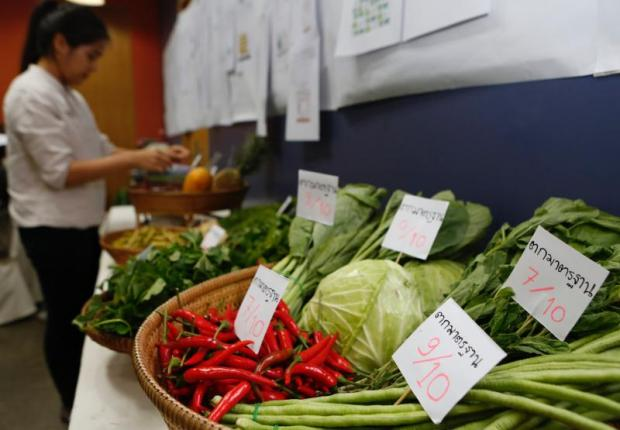 A member of Thai-PAN arranges produce at a press conference held yesterday to alert consumers to the widespread use of harmful pesticides. (Photo by Pattarapong Chatpattarasill)