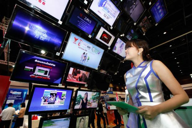 above A model looks at digital TV screens at an exhibition in Bangkok. More people are turning to OTT streaming services.JIRAPORN KUHAKAN