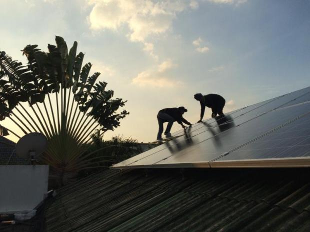 Workers install solar panels on a house, which can help residents cut down on their electricity bills.WEERABOON WISARTSAKUL