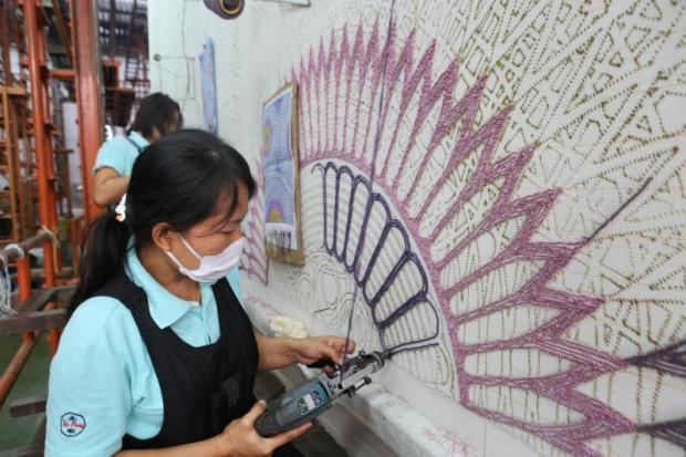 Workers weave carpets at TCMC's factory in Bangkok.