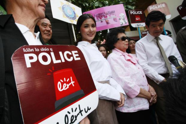 Celebrities Primrada 'Chacha' Detudom, centre, and Wasu 'Jip' Saengsingkaeo, far right, attend the police launch of a new mobile phone app 'Police i Lert u,' which allows people to directly contact officers in case of an emergency over the New Year holiday.Pornprom Satrabhaya