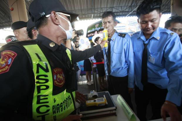 Bus drivers take a breath test during a random check at Mor Chit bus terminal as part of a campaign to boost road safety ahead of the New Year holiday. (Photo by Pornprom Satrabhaya)