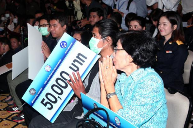Call centre scam victims express their thanks yesterday as they receive money the Anti-Money Laundering Office, police and banks retrieved from gangs.(Photo by Apichart Jinakul)