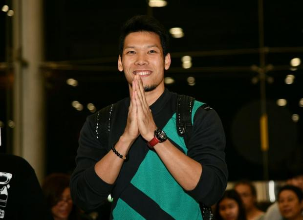 Kawin Thamsatchanan acknowledges his fans with a traditional wai at the airport.