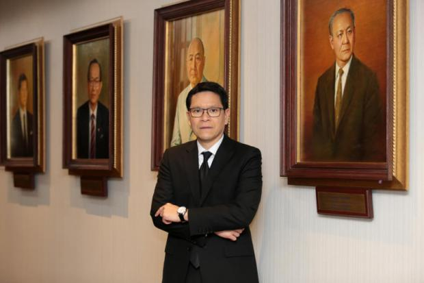 Mr Veerathai stands before portraits of former Bank of Thailand governors.