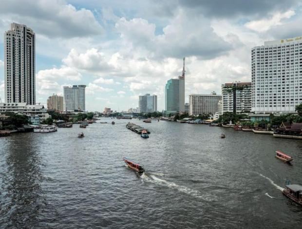 Commuter boats and barges ply the Chao Phraya River in Bangkok.