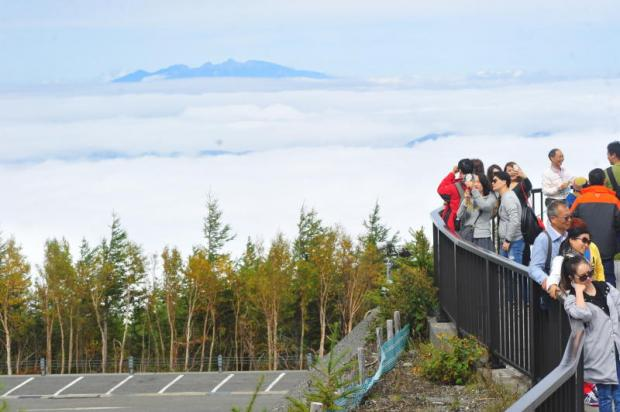 Tourists enjoy stunning scenery above the clouds at the fifth station, the starting point for an ascent of Mount Fuji in Japan. Peerawat Jariyasombat