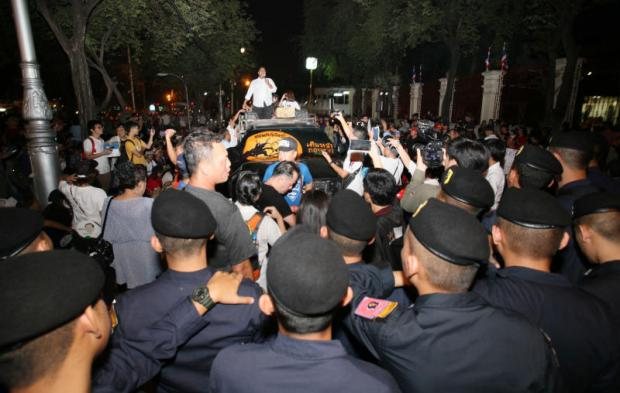 tense situation: Security officers are deployed to maintain order at the rally by the People Who Want Elections outside the Royal Thai Army headquarters on Ratchadamnoen Avenue yesterday. Right: Police confront the protesters as they try to get onto the road.