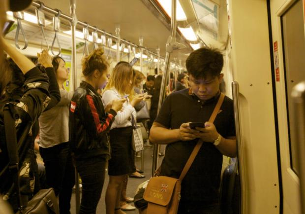 People use their smartphones while traveling on underground train. (Photo by Apichit Jinakul)
