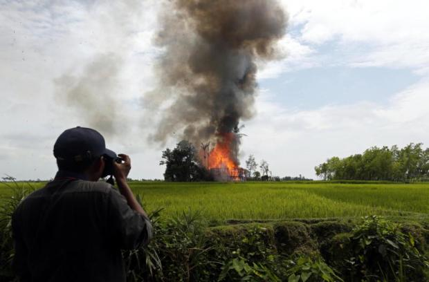 A journalist takes photos of a burning house at a village in Rakhine state in September last year. As Rakhine is off-limits, most media stories from there are done as part of tours set by the state. EPA