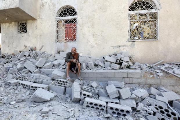 A Yemeni sits among the rubble of his house allegedly hit by an alleged Saudi-led airstrike at a neighborhood in Sana'a on Saturday.(EPA photo)