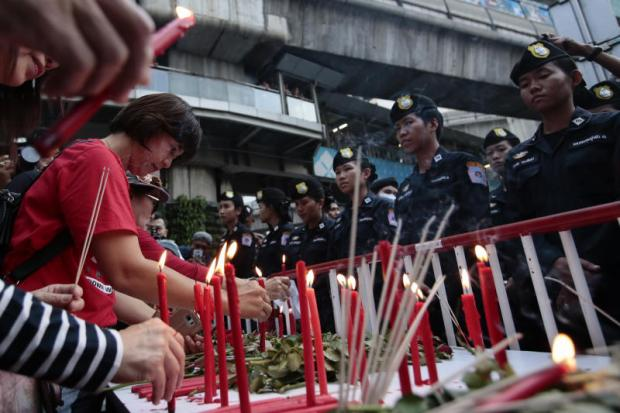 bleeding red: Security officers face people who lit candles near the Ratchaprasong intersection in remembrance of the bloody clash between red shirt protesters and security forces on May 19, 2010.