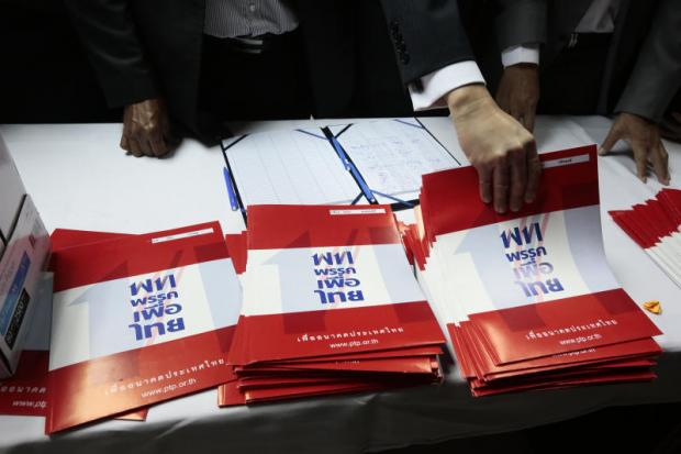 Pheu Thai Party faithful hand out party literature ahead of the poll. The major parties are releasing policy gradually, but agree they will have to make a bigger effort to reach out to a diversifying electorate. (Photo by Patipat Janthong)