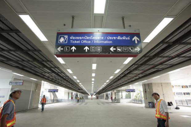 Officials inspect an overhead sign at the Thung Song Hong Red Line electric train station. (PHoto by Patipat Janthong)