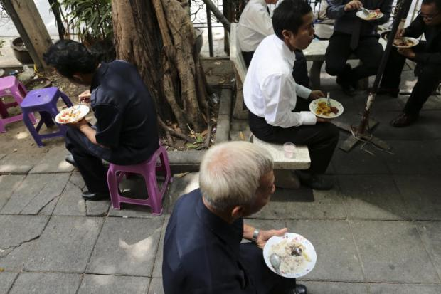 People from all walks of life have lunch on the streets of the capital. Despite a general economic uptick, household purchasing power remains muted. (Photo by Patipat Janthong)