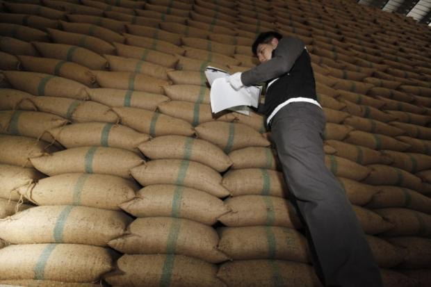 An official inspects documents for the state's rice stores at a warehouse in Khlong Sam Wa district, Bangkok. PATTANAPONG HIRUNARD